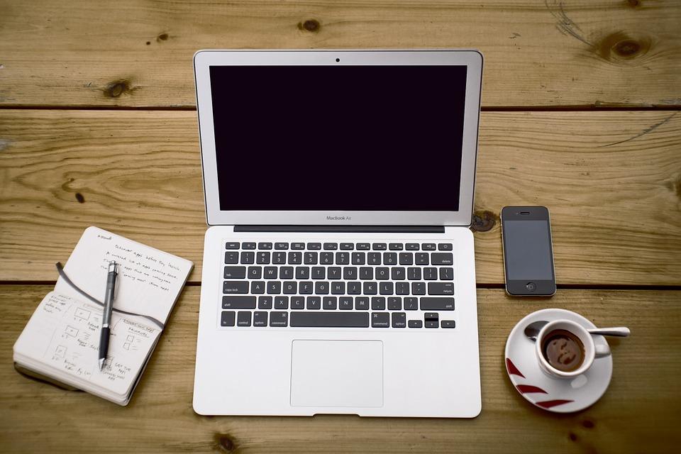 Auf dem Bild ist ein aufgeklappter Laptop zu sehen, neben dem ein Notizbuch und ein Handy liegen.
